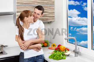 Embracing young enamoured couple at kitchen