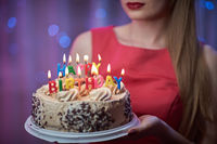 Beautiful girl holding cake with candles.