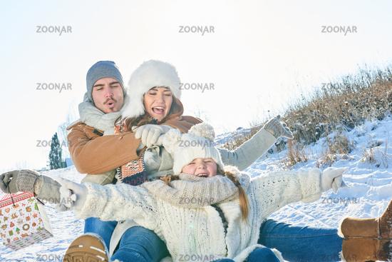Familie hat Spaß  beim rodeln im Schnee