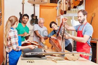 Gruppe Gitarrenbauer mit Lehrlingen und Azubis