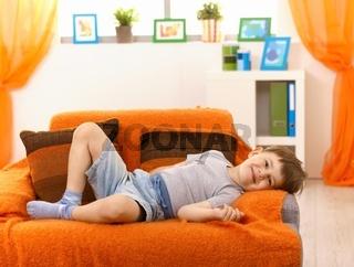 Cute kid relaxing on sofa
