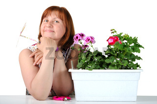 Portrait of pretty middle-aged woman with pelargoniums in a flower pot.