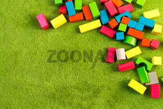 Colorful wooden blocks for children on green carpet