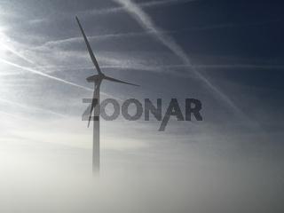 Windrad im Fruehnebel mit Kondensstreifen am Himmel