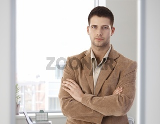 Casual office worker standing arms crossed