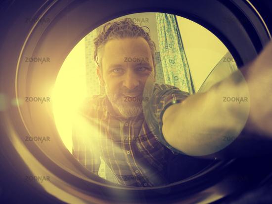 Happy man loading washing machine
