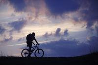 Man mountain bike clouds blue