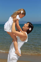 Mother lifting daughter on beach