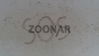 Top view photo of SOS written in sand on tropical beach