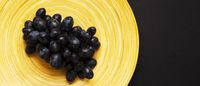 Black Grapes on Wooden Platter