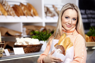 The young girl with bread in shop
