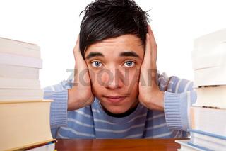 Junger trauriger Student mit Büchern hat Prüfungsstress