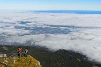 Touristen blicken vom Gipfel Pilatus auf die vom Wolkenmeer teilweise bedeckte Stadt Luzern
