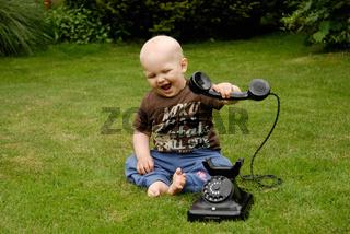 Kind mit einem antiken Telefon