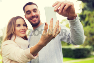 close up of couple with smartphone taking selfie