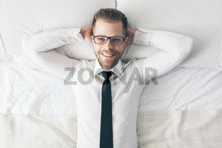 Top view. Young handsome businessman with glasses lying on the bed