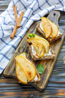 Crostini with ricotta and pears on a wooden board.