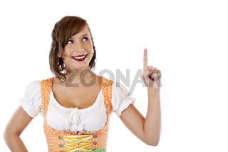 Schöne Frau mit Oktoberfest Dirndl zeigt auf Werbefläche
