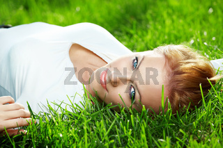 Portrait of beautiful young woman lying on a fresh green lawn
