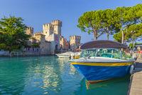 Motorboot im Hafen von Sirmione vor dem Castello Scaligero am Gardasee, Brescia, Lombardei, Italien