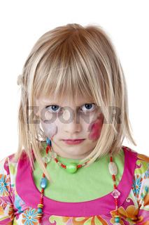 Blondes verkleidetes Mädchen mit geschminkten Wangen schaut ernst.Freigestellt auf weissem Hintergrund.