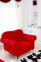 Red classical armchair and white curtains