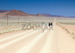 Two motorbikes driving fast on long straight desert road.