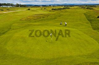 Zwei Golfspieler beim Putten auf dem Grün auf der Golfanlage St Andrews Links, Schottland, UK