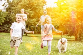 Familie mit Hund beim Laufen im Sommer