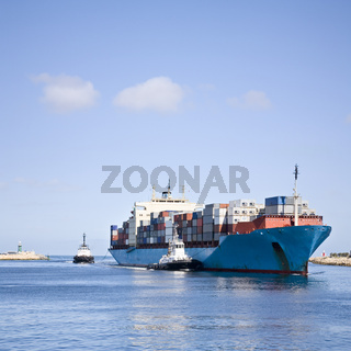 Massive Container Ship Entering River Mouth Assisted by Two Tugs