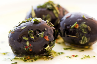 Pickled black olives with Italian herbs in olive oil as closeup on a white plate