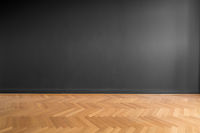 empty room with black wall background and wooden parquet floor