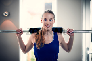 Portrait of woman with barbell