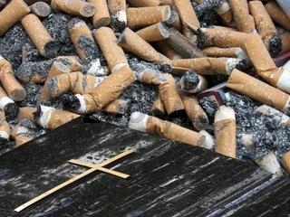 Grabstein hinterlegt mit Zigarettenkippen mit Zigarettenasche und einer Zigarettenschachtel