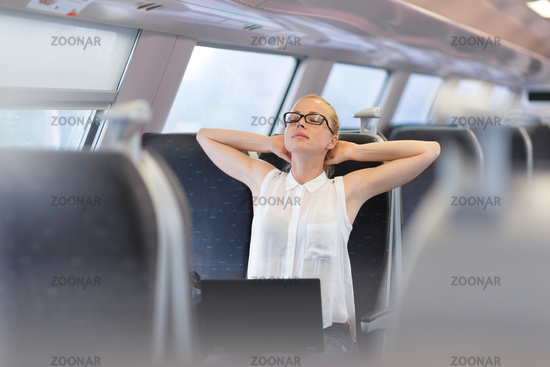 Woman streching while travelling by train.