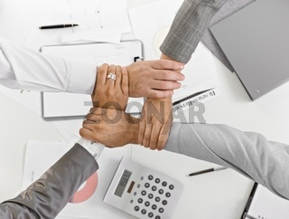 Four hands together in unity at businessmeeting