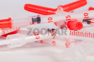 Pile of Empty Syringes with Red Safety Caps