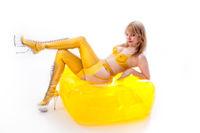 Blonde Frau in gelbem durchsichtigen Latex Outfit auf aufblasbarem Stuhl