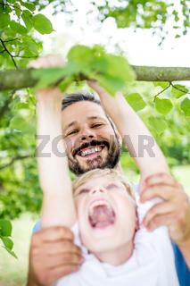 Vater hilft seinem lachenden Sohn
