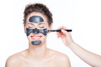 Black charcoal mask application on beautiful woman.