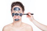 Black charcoal mask application on beautiful woman.