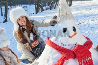 Mutter und Tochter bauen einen Schneemann