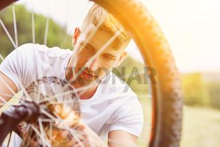 Mann beim Reifen vom Fahrrad reparieren