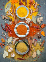 Various of spices and herbs in ceramic bowl. Flat lay of spices ingredients chilli ,pepper corn, garlic, thyme, oregano, cinnamon, star anise, nutmeg, mace, ginger and bay leaves on stone background.