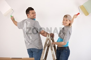 Smiling couple painting wall together