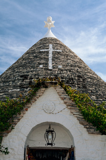 Symbol in the Trullo conical rooftop in Alberobello, Puglia, Italy
