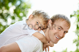 Portrait of laughing father and son piggyback