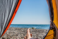 Image human legs lying in tourist tent with view of the sea