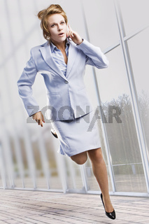 Beautiful businesswoman running with mobile phone.