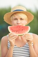 Beautiful girl in straw hat eating fresh watermelon. Film camera style